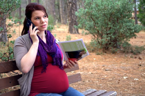 Pregnant woman talking on the phone at a park