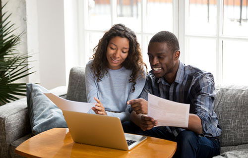Young mixed-race couple looking at laptop in living room